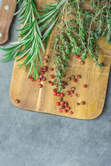 Fresh Provence Herbs Rosemary Thyme Twigs red Pink Peppers on Aged Wood Cutting Board Knife on Dark Concrete Stone Table. Top View. Mediterranean Cuisine Meat Fish Seasoning Ingredients. Copy Space