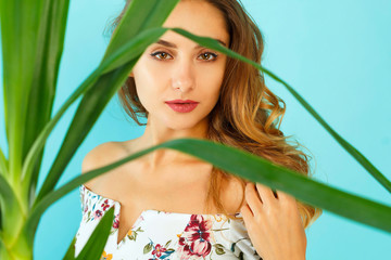 Beautiful attractive woman standing near green plant over blue background