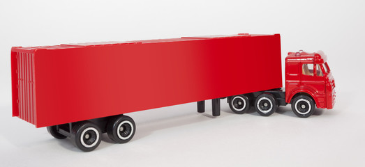 Red plastic toy semi truck cab with trailer container. Isolated.