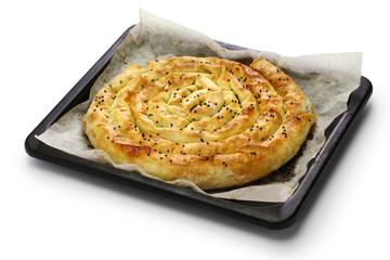 homemade kol borek, turkish savoury rounded pie on oven tray isolated on white background