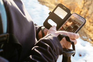 hiker uses application on smartphone during hike