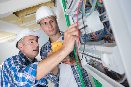 tradesmen installing a distribution board