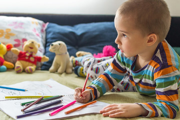 Little child boy drawing with color pencils. Children's creativity.