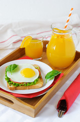 Sandwich with fried egg, tomato and greens