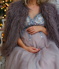 pregnant girl sits on the couch in a blue dress with sparkles in a fur cape