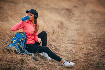 Young woman hiker resting on mountain and drinking water