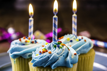 three yellow cupcakes with blue frosting and rainbow sprinkles on blue plate with burning birthday candles