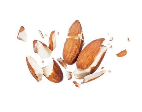 Almonds is torn to pieces close-up, isolated on white background