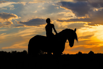 Silhouette of man riding a horse on sunset with beautiful cloudy background