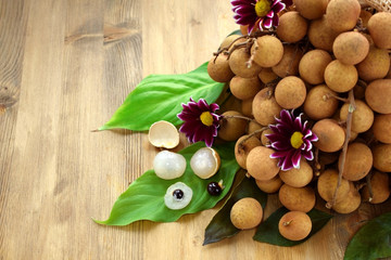 Bunch of longans and peeled fruits on wooden background