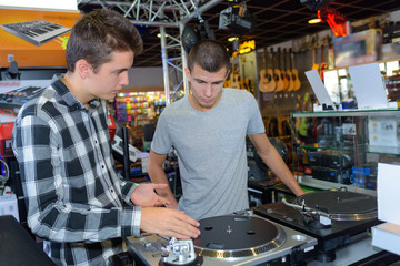Young men looking at turntables