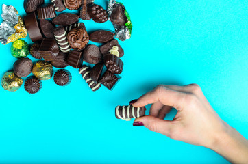 female hand takes a candy from a handful of chocolates assorted, which lie in the corner of a frame on a blue background