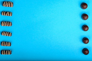 on a blue paper background are symmetrically laid out chocolate candies of different shapes