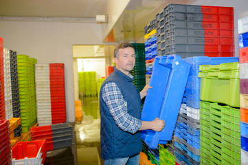 Man taking crate from stack