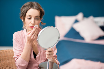 Young woman removing makeup with a cotton swab sitting in the blue bedroom