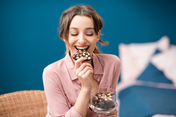 Beautiful woman enjoying a chocolate sitting on the blue wall background indoors