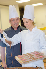 cheerful young professionals pastry cooks preparing a chocolate dessert