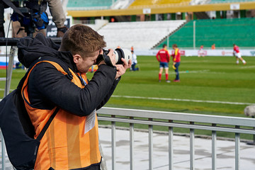 man taking pictures of the match
