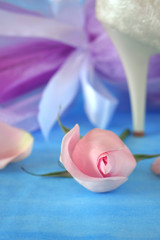 Wedding composition. Close-up of a pink rose. High-heeled shoe and gift wrap in the background