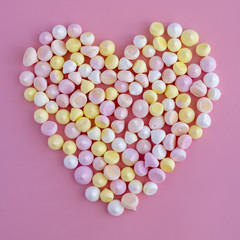Multicolored meringues made in the shape of a heart on a pink background