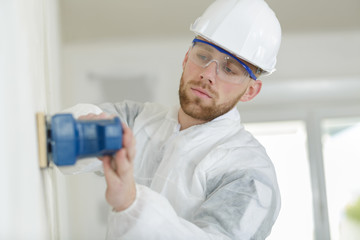 male construction worker smoothing wall surface