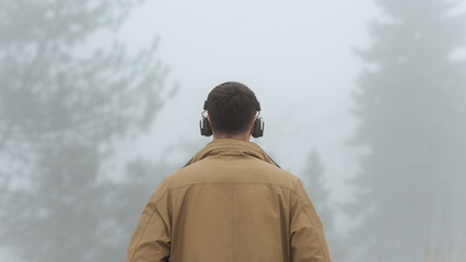 Horizontal rear view of young handsome male walking in misty nature, listening to music outside. Unrecognizable man wearing trendy coat, black bluetooth headphones on head. People, technology concept.