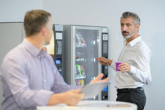 man taking coffee from vending machine
