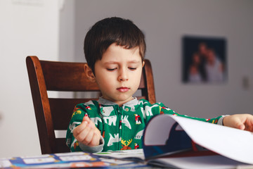 Cute boy reading a book while sitting at table, indoor shoot. Little boy having fun during studying. Best picture for child education concept.
