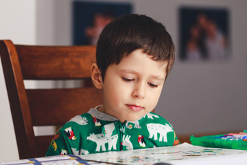 Pretty little boy reading a book while sitting at table, indoor shoot. Little boy having fun during studying. Best picture for child education concept.