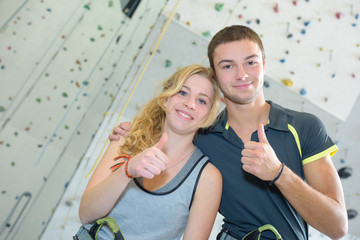 Young couple giving thumbs up in front of climbing wall