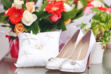 Gorgeous bride shoes decorated with crystals on floral background. Beautiful white shoes encrusted with crystals, isolated on decorative background. Best picture of women shoes for wedding projects.