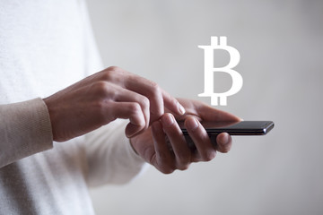 man hand phone with bitcoin sign in screen