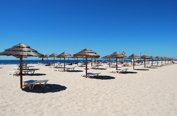 Many Umbrellas on the beach with blue sky in Tavira island,Portugal