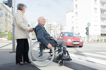 wife and elderly person in a wheelchair crossing the road