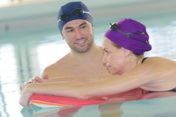 man helping woman in swimming pool with float