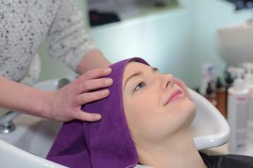 female hairdresser washing woman client hair