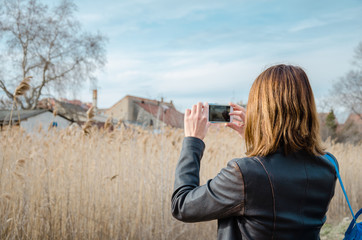 Young urban brunette woman taking photo of countryside