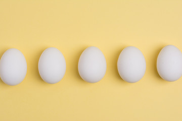 Happy Easter concept. White eggs on yellow background close up. Flat lay. Minimal concept. Top view. Design, visual art.