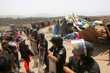 Police guard as people stand around after police evict squatters from a land in Villa El Salvador, on the outskirts of Lima