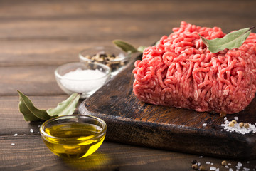 Fresh raw beef minced meat with salt, pepper, olive oil and laurel leaves on dark wooden board. Healthy food concept with copy space.