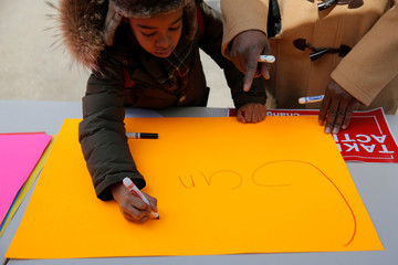 Barack Tillard, 8, creates a sign with the help of his father Conrad Tillard before a rally held at the Prospect Park Bandshell for the National School Walkout in Brooklyn, New York