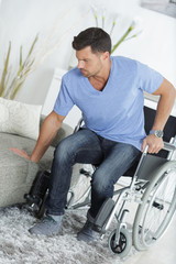 young handsome handicapped man going from wheelchair to sofa