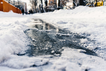 Slippery shiny ice on the sidewalk in winter under the snow beckons to ride on it to enjoy