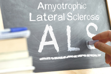 Blackboard hand writing the ALS acronym next to some science books in a university classroom.