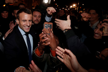 French president Emmanuel Macron shakes hands with residents in front of the city hall of Tours
