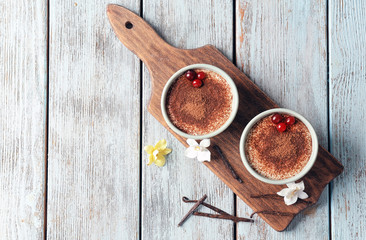 Composition with tasty vanilla pudding on light wooden background, top view
