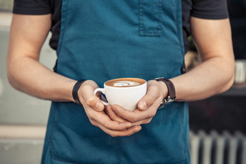 Barista holding  a cup of coffee with latte art