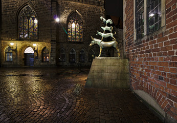 Statue of the Bremen Musicians at night with the historic city hall and the Church of our Lady in the background