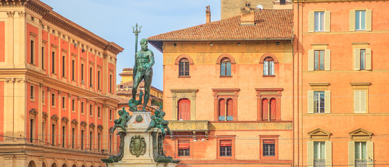 Architecture panorama of Bologna city in Emilia region of Italy. Neptune bronze statue and restored fountain, with historic orange-red buildings background in Nettuno square of the town center.