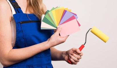 Junge Frau sucht eine Farbe aus um die Wand zu streichen
